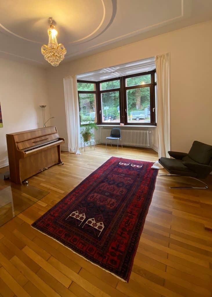 Einzelner Raum mit Klavier, Perserteppich und Kronleuchter